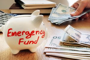 Emergency fund written on a piggy bank near two small stacks of cash
