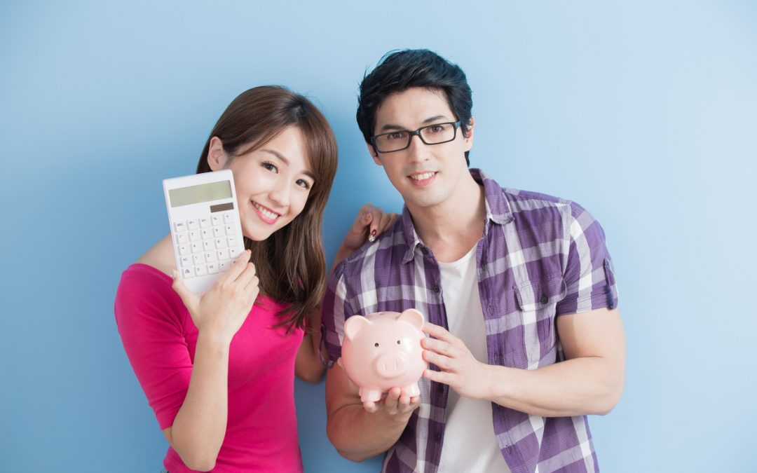 Young casually dressed couple holds classic piggy bank and calculator. To illustrate how to save for retirement.