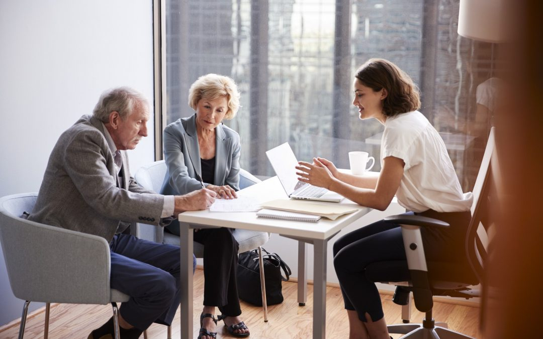 Seniors sign documents in meeting with financial adviser in office. To illustrate: Do I need an estate plan?